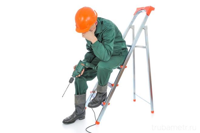 строитель сидит с дрелью на стремянке