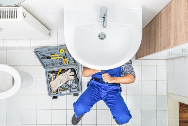 сантехник под раковиной в ванной