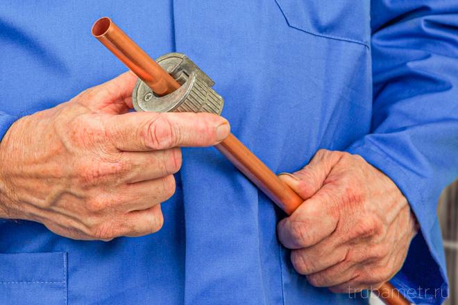 Мастер с труборезом на медной трубе.