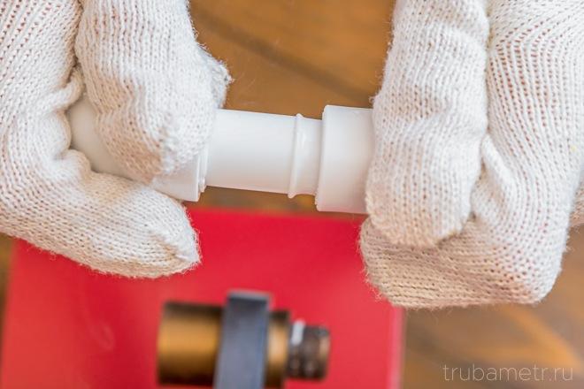 сантехник в перчатках соединяет разогретые пп трубы