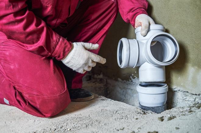 Работник осуществляет монтаж канализации
