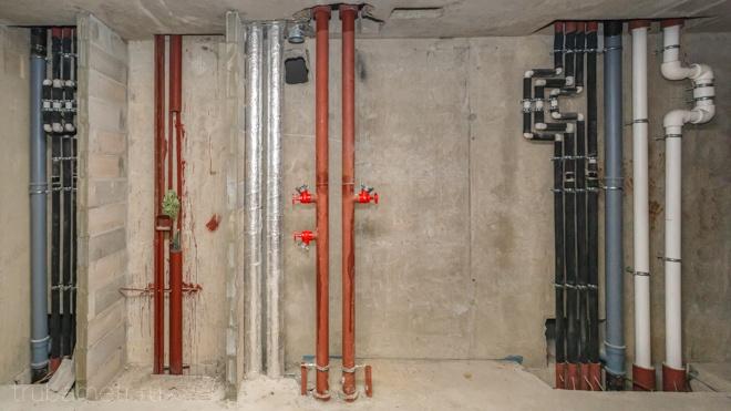 Трубы системы отопления и водоснабжения в изоляции на сером фоне