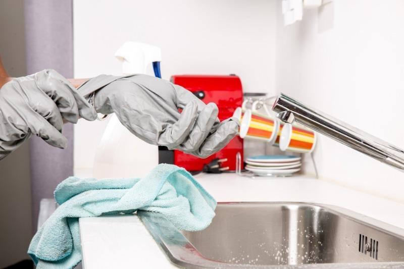 Руки в защитных перчатках и мойка